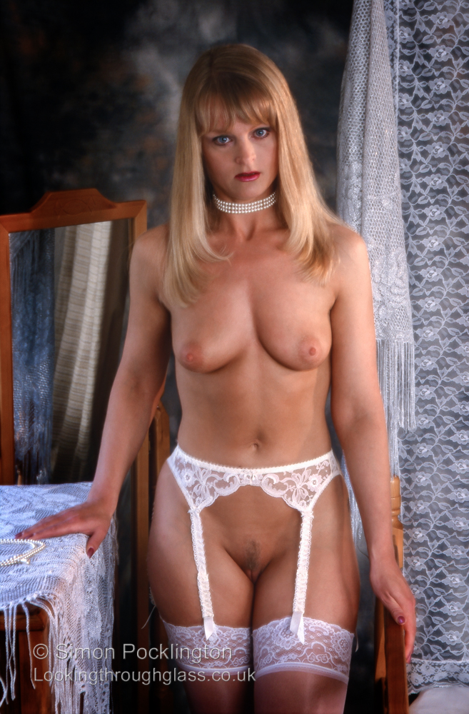 Professional nude model in stockings and suspenders